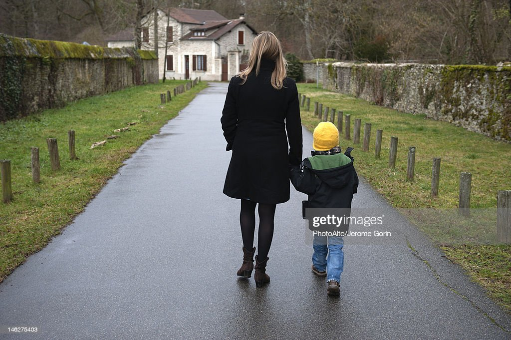 Mother and son walking on path in village, holding hands, rear view
