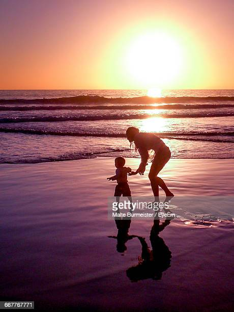Mother And Son Walking On Shore During Sunset