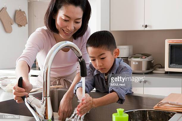 Mother and Son Washing Hands in Kitchen