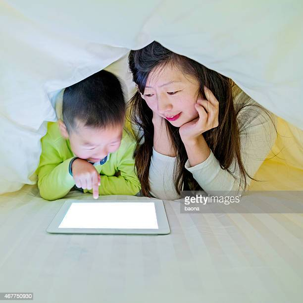 Mother and son watching digital tablet in bed