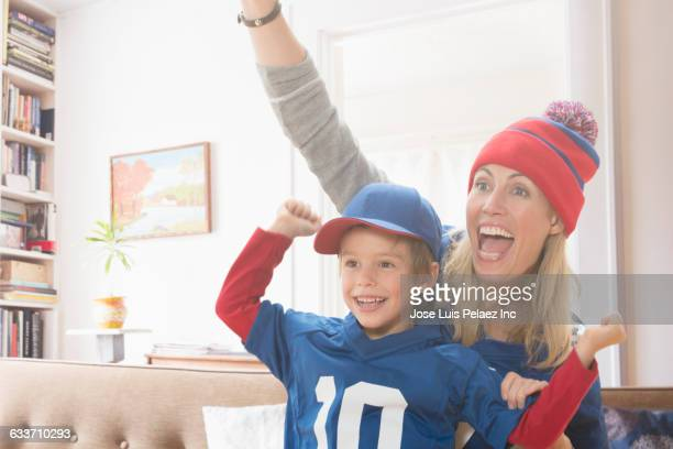 Mother and son watching sports in living room