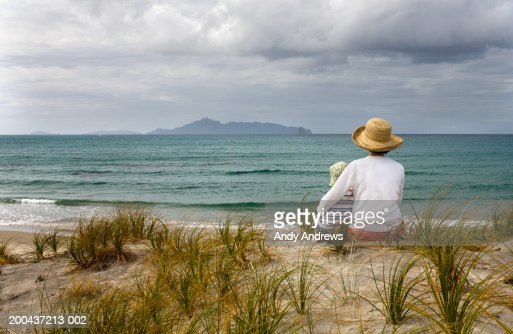Mother and son (2-4) wearing sun hats sitting on beach, rear view. : Foto de stock