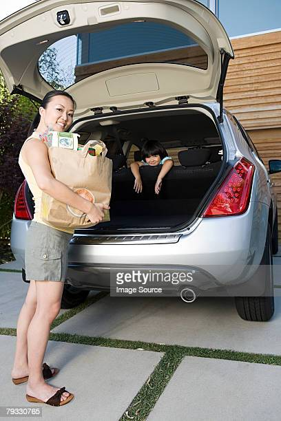 Mother and son with car and shopping