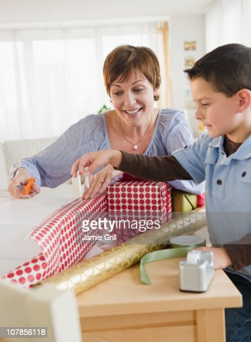 Mother and son wrapping presents together : Stock Photo