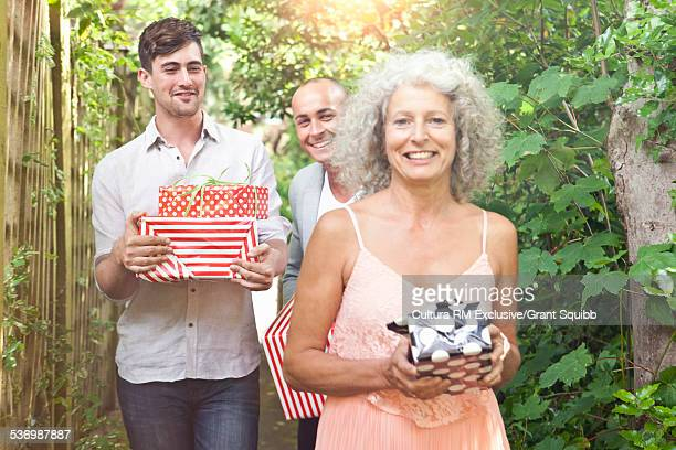 Mother and sons carrying gifts along garden path for surprise birthday party