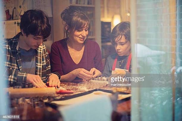 Mother and sons making gingerbread cookie at home through window.