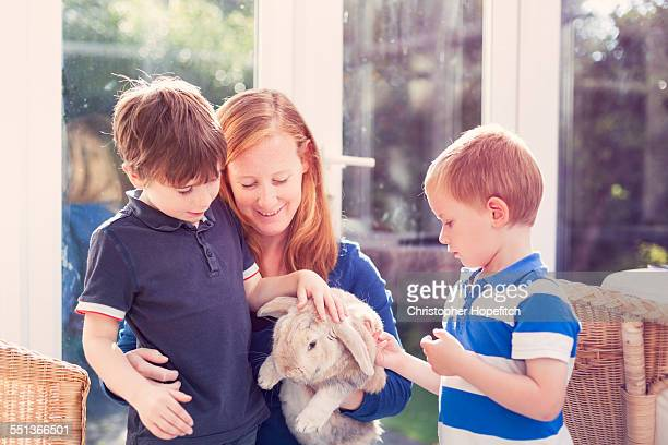 Mother and sons petting a rabbit
