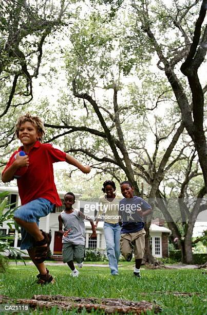 Mother and sons (5-7) playing football on lawn