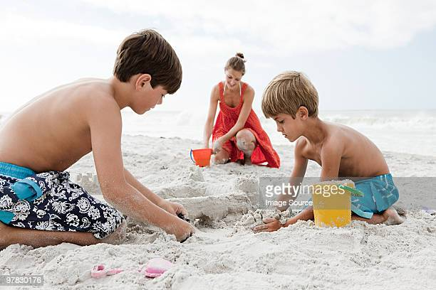 Mother and sons playing in sand