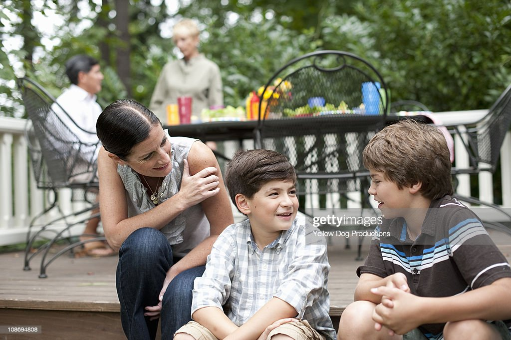 Mother and sons talking at neighborhood BBQ : Stock Photo