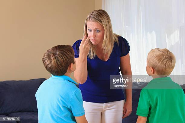 Mother and sons with hearing impairments signing look at me in American sign language