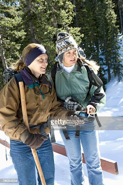 Mother and teenage daughter hiking in snow