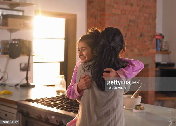 A mother and teenage daughter hugging warmly