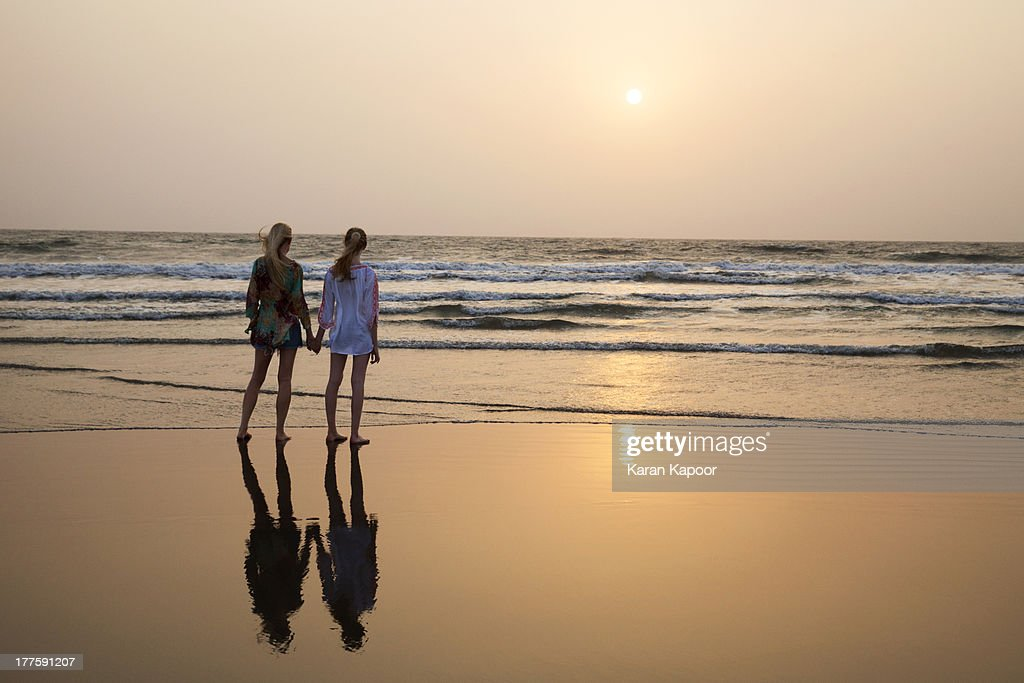 Mother and teenage daughter looking at sunset on b : Stock Photo