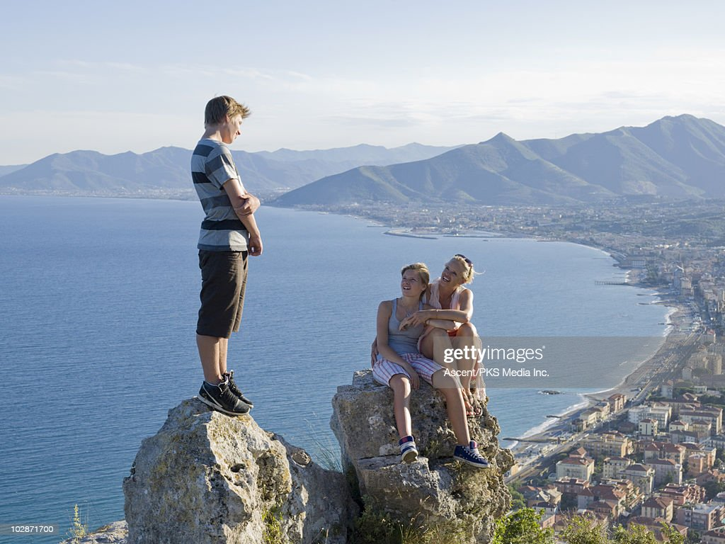 Mother and teenage kids resting on rocks : Stock-Foto