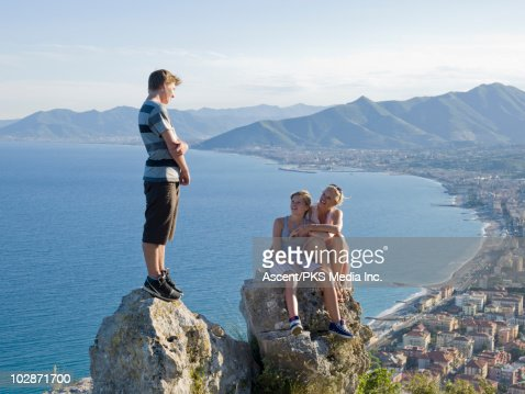 Mother and teenage kids resting on rocks : Photo