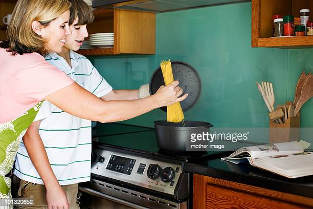 Mother and teenage son making pasta