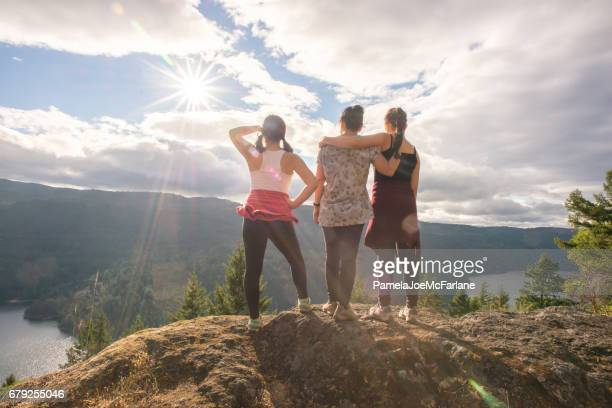 Mother and Teenager Daughters Hiking and Enjoying View from Summit