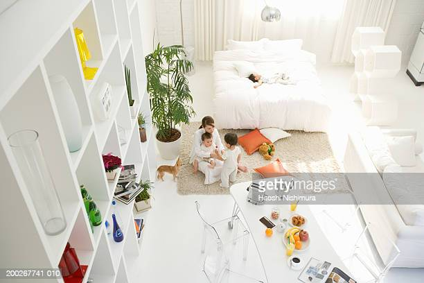 Mother and three children (6-21 months) in living room, elevated view