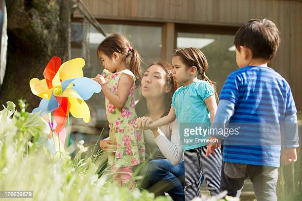 Mother and three children with toy windmill in garden