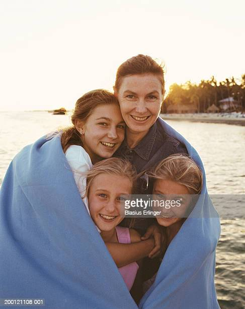 Mother and three daughters (7-18) wrapped in blanket, portrait