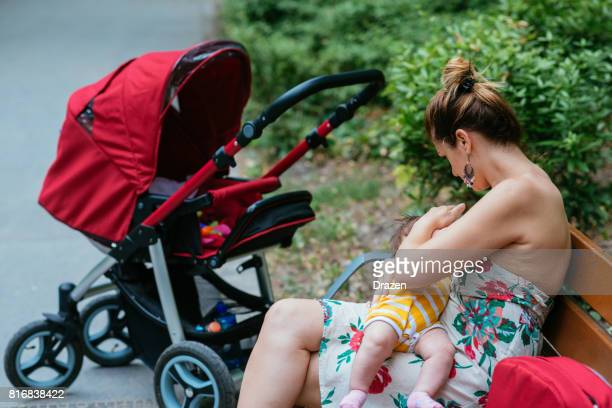 Mother and three month old baby breastfeeding in park
