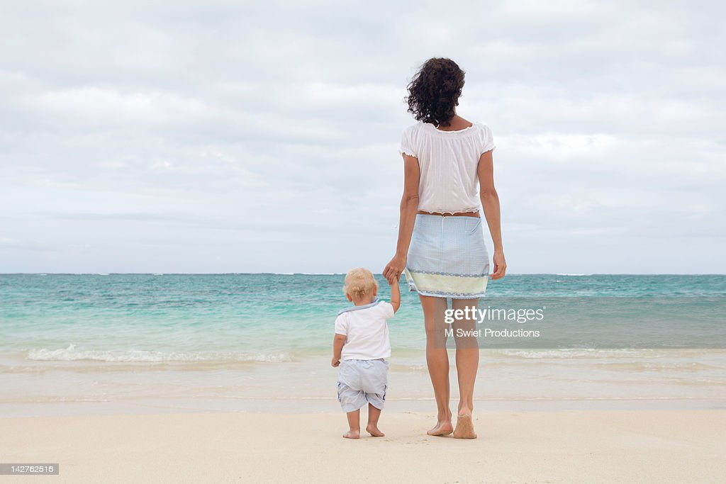Mother and toddler child standing on beach : Stock Photo