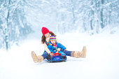 Young mother and her little toddler daughter enjoying a sledge ride in a snowy park