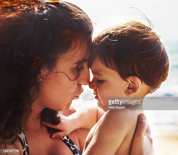 Mother and toddler kissing on beach