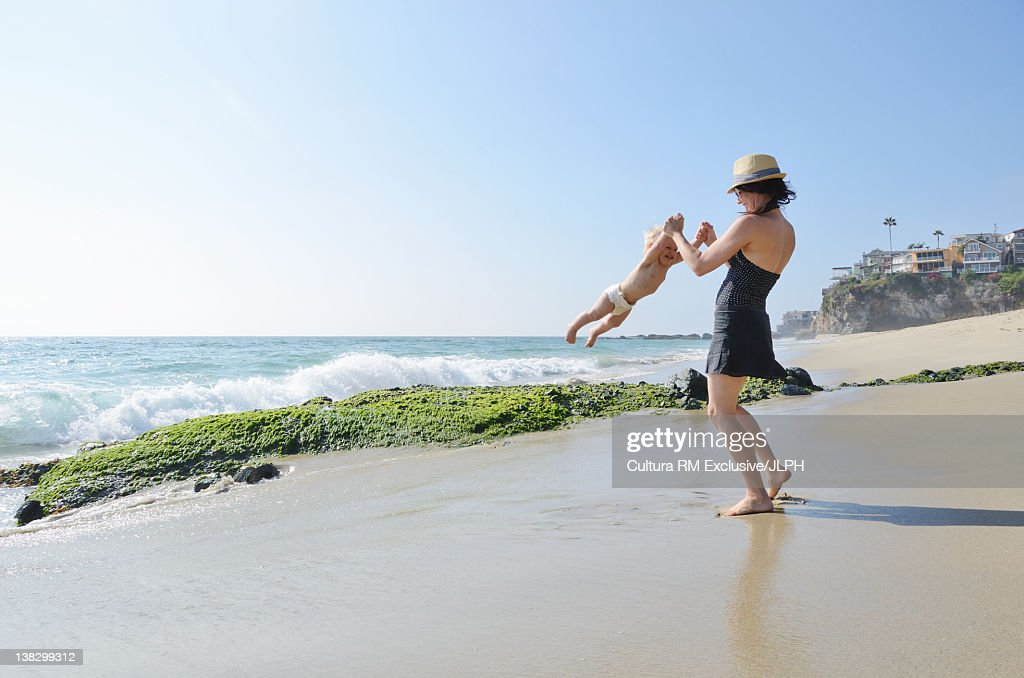 Mother and toddler playing on beach : Stock Photo