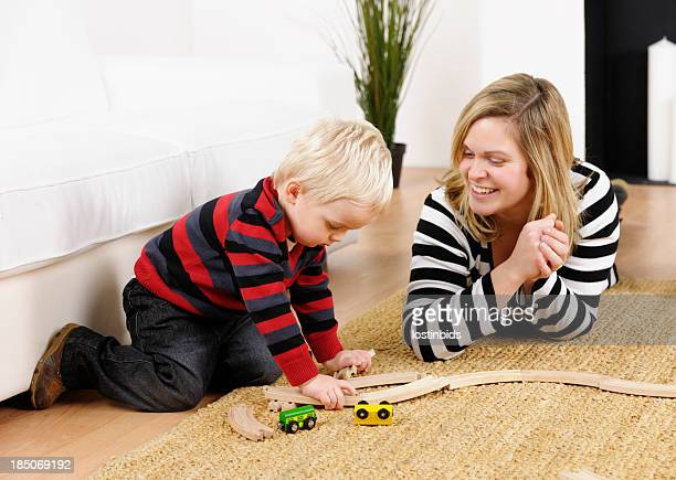 Mother And Toddler Playing With Train Set In The Lounge