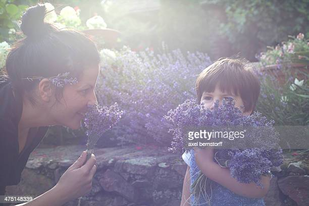 Mother and toddler son smelling bunch of lavender