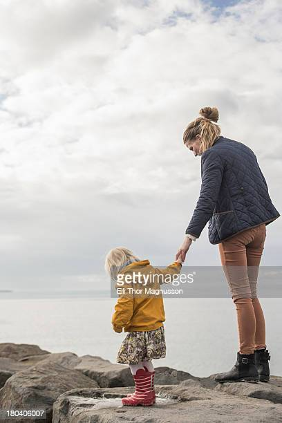 Mother and toddler walking on harbor wall
