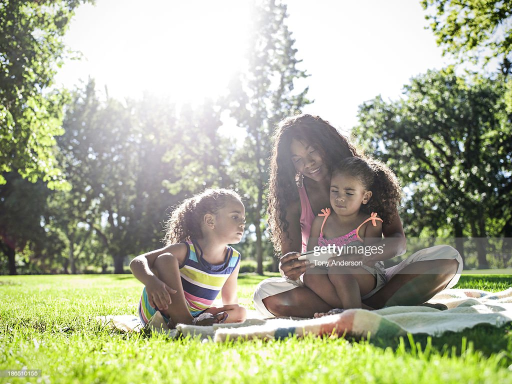 Mother and twin daughters looking at mobile device : Stock Photo