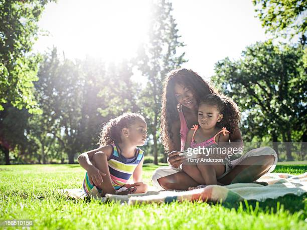 Mother and twin daughters looking at mobile device