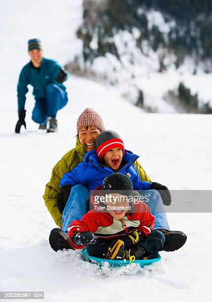Mother and two boys (4-6) sledding down hill, father in background