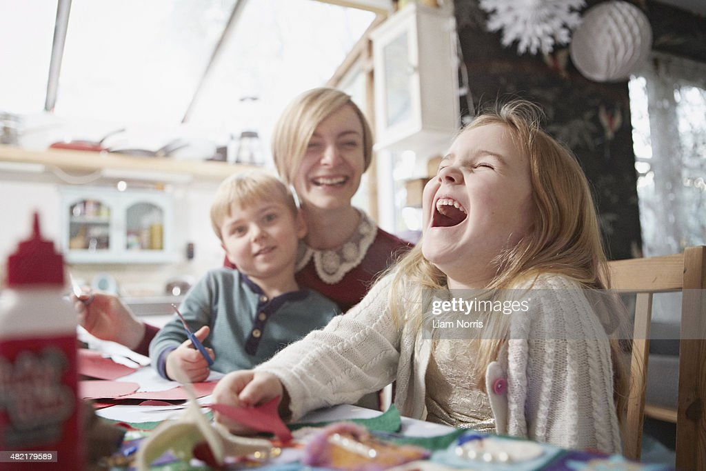 Mother and two children craft making at kitchen table : Stock Photo