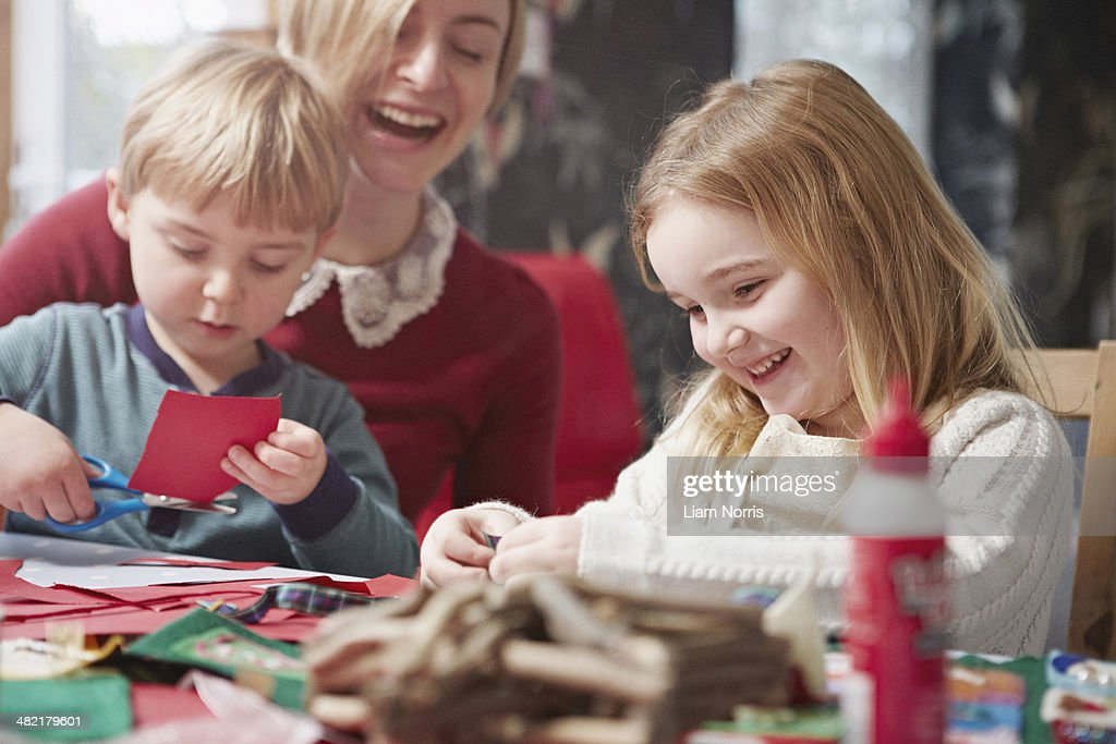 Mother and two children crafting at kitchen table : Stock-Foto