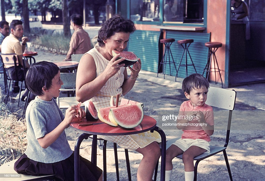 mother and two children eating watermelon outdoors : Stock Photo