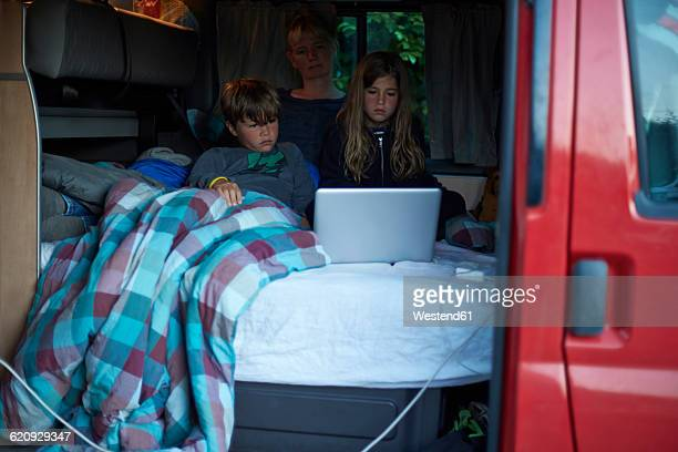 Mother and two children sitting on bed in a camper watching a movie with laptop