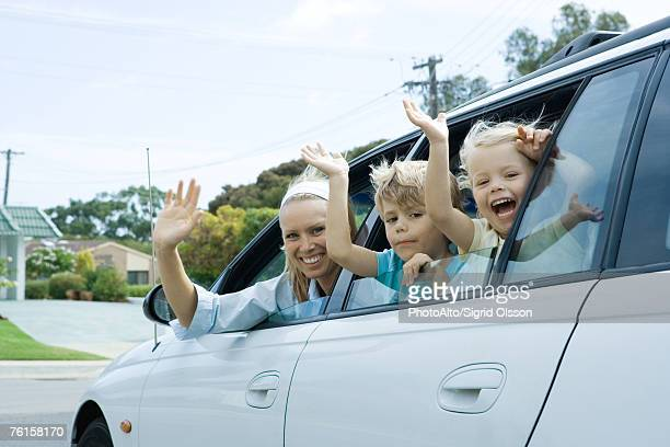 'Mother and two children waving out of car windows, looking at camera'