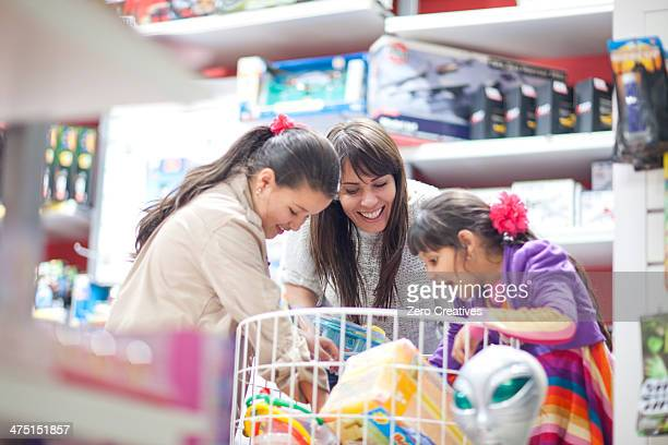 Mother and two daughters choosing toys