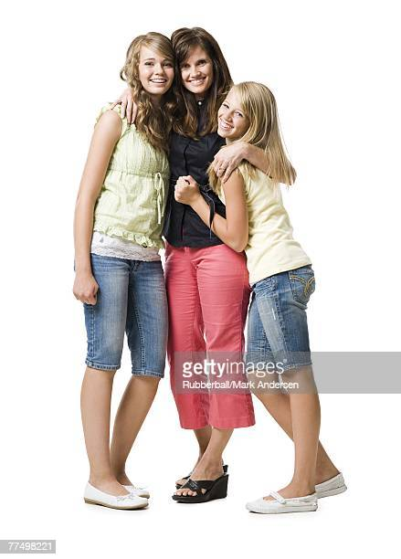 Mother and two daughters embracing and smiling