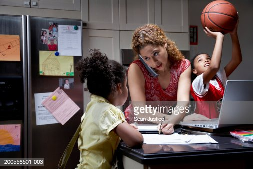 Mother and two daughters (8-12) in kitchen : Stock Photo