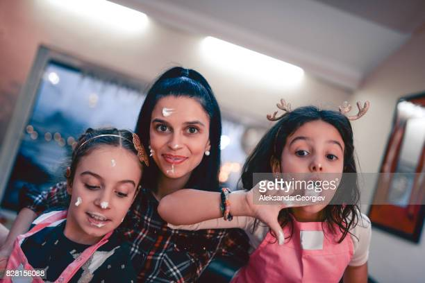 Mother and Two Daughters Making Cake and Frosting and Having a Great time