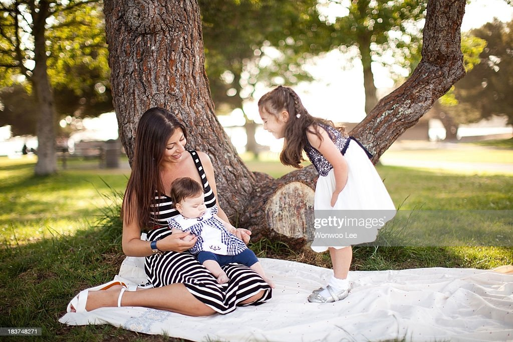 Mother and two daughters on picnic blanket : Stock Photo