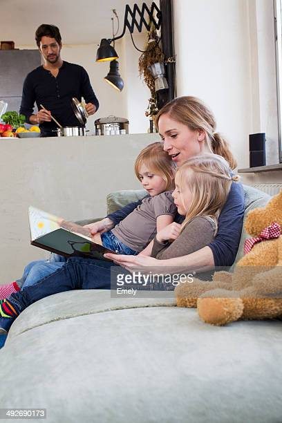 Mother and two daughters reading storybook