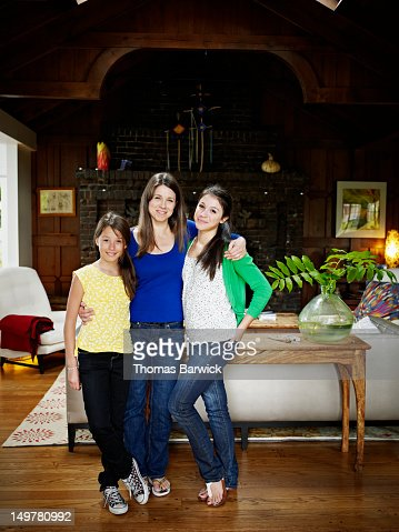 Mother and two daughters standing in entry of home : Stock Photo