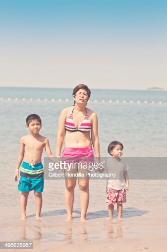 Mother and two kids on the beach, looking bored : Stock Photo