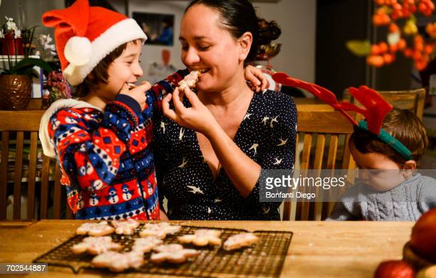 Mother and two sons at table eating home-baked Christmas biscuits